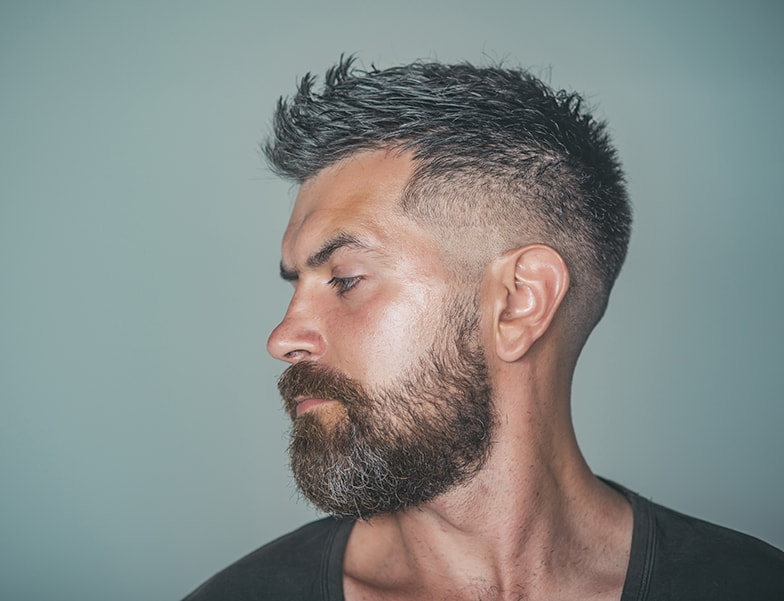 Man with bearded face profile and stylish hair pose on grey background. Barber, barbershop, hairdresser or beauty salon concept, copy space